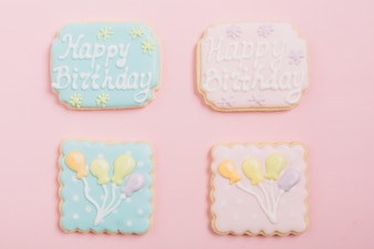 Overhead view of icing cookies over pink background