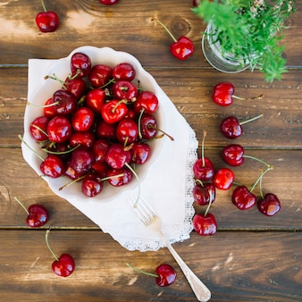 Overhead view of juicy red cherries in bowl on wooden background