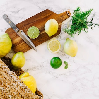 Overhead view of lemon and knife on wooden chopping board