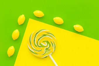 Overhead view of lemon candies and lollipop on dual yellow and green background