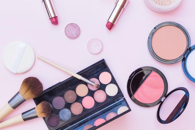 化粧ブラシのオーバーヘッドビュー;口紅;アイシャドウ;ピンクの背景にスポンジとブラッシャー