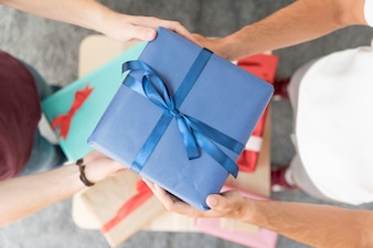 Overhead view of male friend's holding blue wrapped gift box with tied ribbon