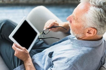 Overhead view of man holding digital tablet and eyeglasses