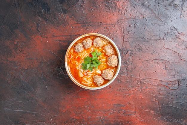 暗い背景の茶色のボウルに麺とミートボールスープの俯瞰図