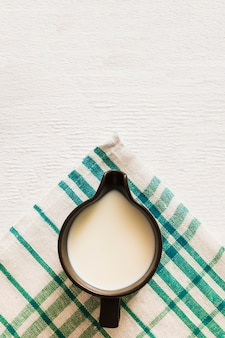 Overhead view of milk in the mug over the cotton napkin