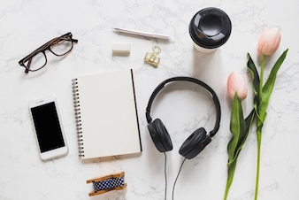 Overhead view of mobile phone; eyeglasses; notebook; stationery; headphone and pink tulips on marble backdrop