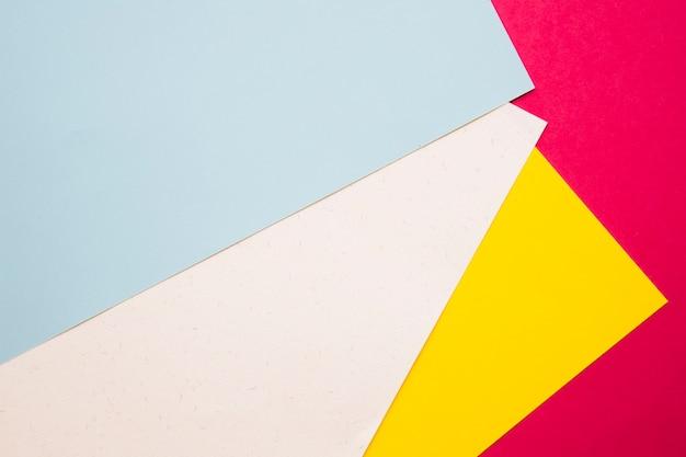 Верхний вид многоцветной картонной бумаги на розовой поверхности