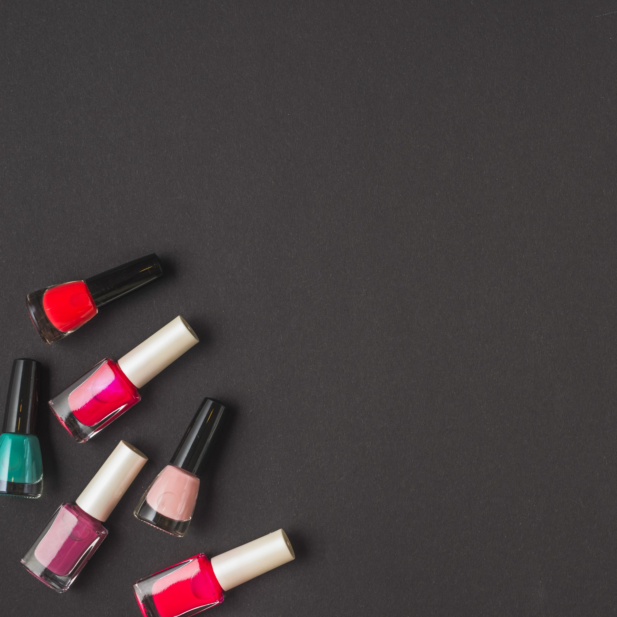 Overhead view of multi colored nail varnish bottles on black surface