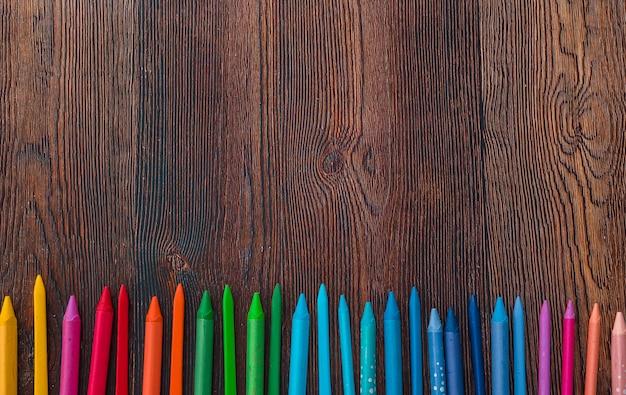 여러 가지 빛깔 왁스 크레용의 오버 헤드보기는 배경의 맨 아래에 행으로 배열