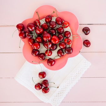 Overhead view of napkin near cherries on flower shaped plate