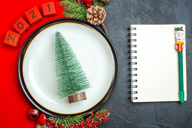 Вид сверху на новогодний фон с елочными украшениями для украшения тарелки еловые ветки и цифры на красной салфетке рядом с блокнотом с ручкой на черном столе