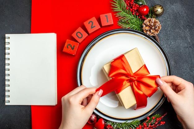 Вид сверху на новогодний фон с подарком на аксессуарах для украшения обеденной тарелки еловые ветки и числа на красной салфетке и блокнот на черном столе