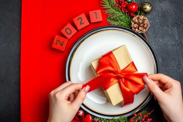 Вид сверху на новогодний фон с подарком на аксессуарах для украшения обеденной тарелки еловые ветки и числа на красной салфетке на черном столе