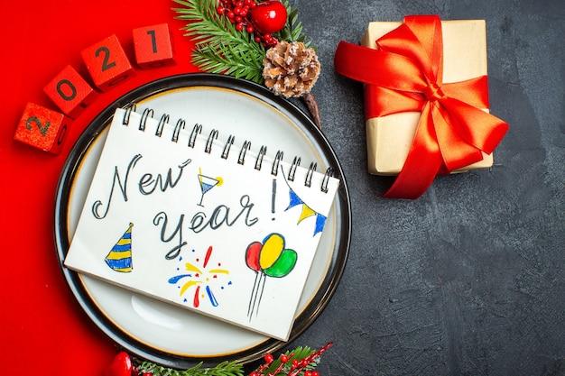 Вид сверху на новогодний фон с блокнотом с новогодними рисунками на тарелке украшения аксессуары еловые ветки и числа на красной салфетке и подарок на черном столе