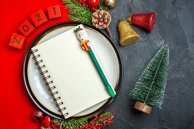 Вид сверху на новогодний фон с блокнотом с ручкой на обеденной тарелке, аксессуары для украшения еловых веток и цифр на красной салфетке рядом с елкой на черном столе