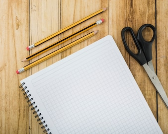 Overhead view of notepad; scissors and pencils on wooden plank