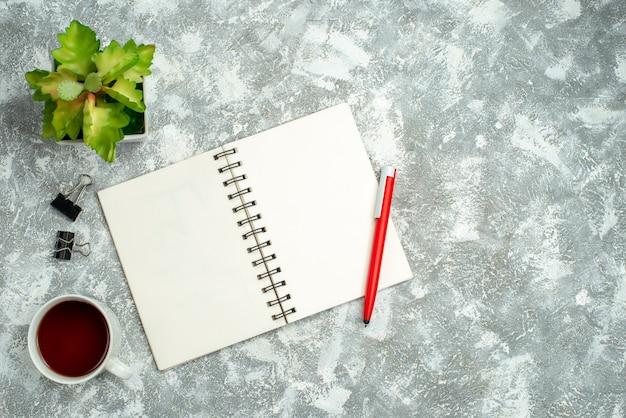 灰色の背景にペンとお茶の植木鉢のカップとオープンスパイラルノートの俯瞰図