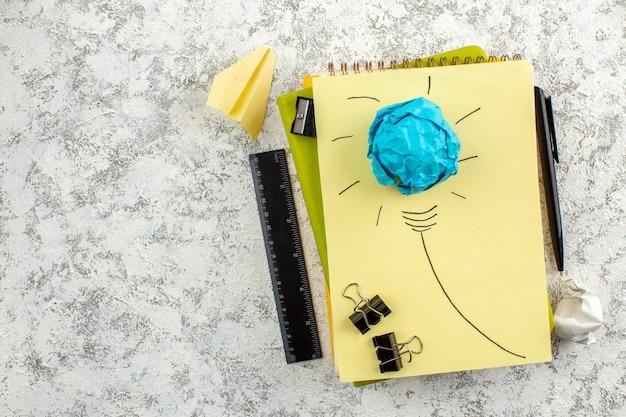 白い表面の左側にある閉じたスパイラル ノートとオフィス アプライアンスの紙の電球の俯瞰