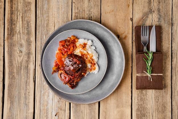 나무 테이블에 ossobuco가 있는 접시의 오버 헤드 보기