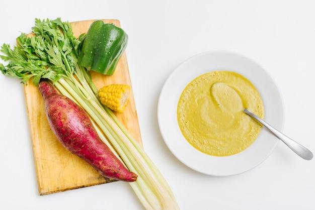 Верхний вид пюре из тыквы возле сырых овощей на белом фоне