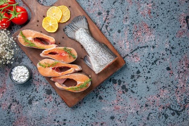 生の魚の俯瞰図レモンスライスグリーンペッパー木製まな板とトマトブルーブラックミックスカラーテーブル