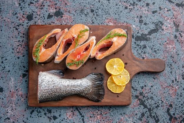 青黒ミックスカラーテーブルの木製まな板に生魚レモンスライス緑コショウの俯瞰図
