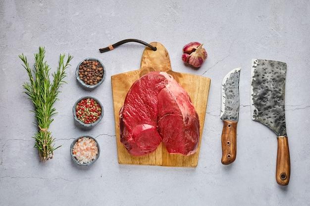 구체적인 배경 위에 향신료와 허브와 원시 신선한 사슴 뼈없는 햄의 오버 헤드보기