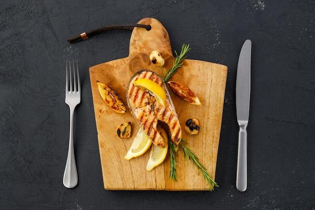 調理の準備ができている木製のまな板上の生のマスステーキの俯瞰図