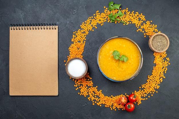 Вид сверху красной чечевицы, выстроенной в круг, и блокнот с вкусным супом и солью и перцем на черном фоне