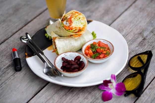木製のテーブルに赤い口紅、食べ物、紫の花の俯瞰。おいしいサラダとスムージーのガラスの横に立っている豆の大皿の写真。