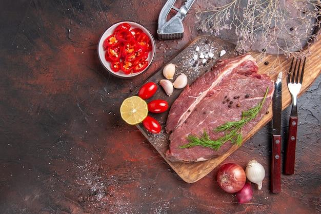 木製のまな板に赤身の肉と暗い背景にニンニクグリーンレモンオニオンフォークとナイフの俯瞰図