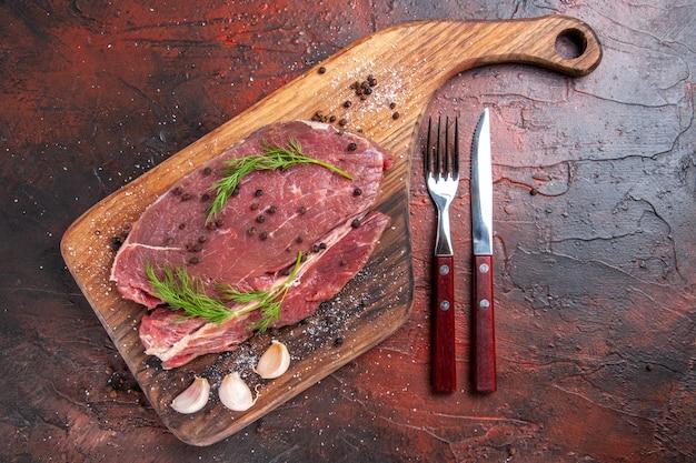 Вид сверху красного мяса на деревянной разделочной доске и чеснока, вилки и ножа с зеленым перцем на темном фоне