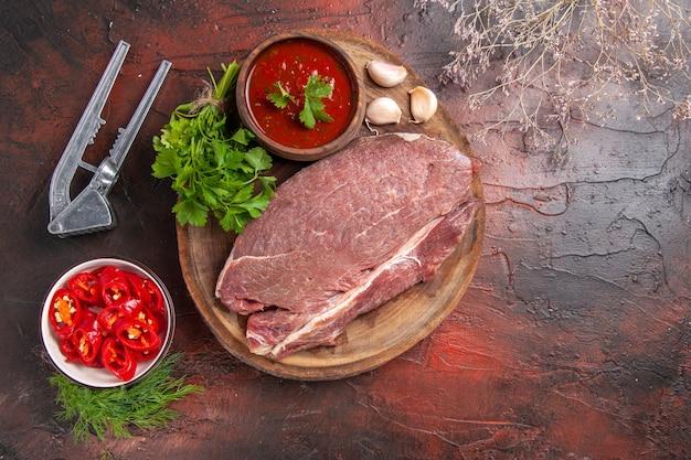 Вид сверху красного мяса на деревянном подносе и чесночного зеленого кетчупа и нарезанного перца на темном фоне