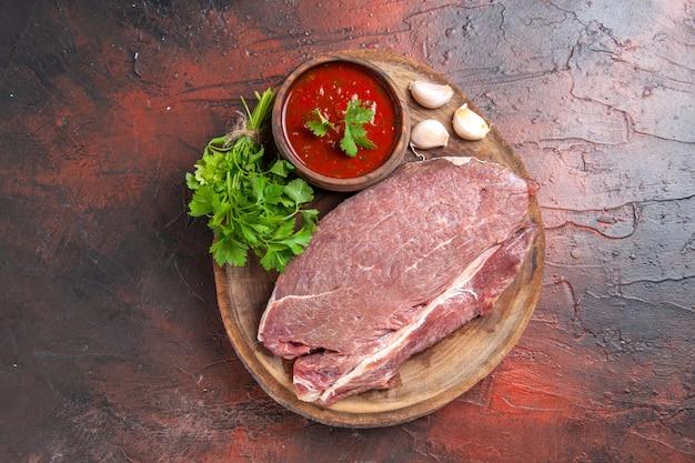 Вид сверху красного мяса на деревянном подносе и чесночного зеленого кетчупа на темном фоне
