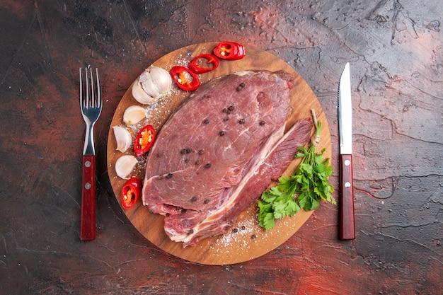 Вид сверху красного мяса на деревянном подносе и чеснока, зеленого лимона, перца, лука, вилки и ножа на темном фоне