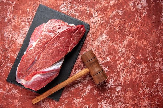 黒のボード上の赤い生の新鮮な肉とパステルカラーの赤い背景の上の茶色の木製ハンマーの俯瞰図