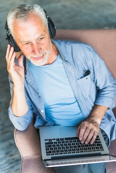 Overhead view of senior man listening music on headphone with laptop