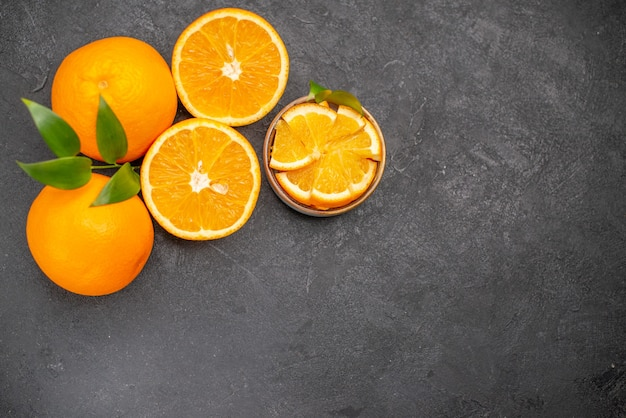 暗いテーブルの上の黄色の全体とみじん切りのオレンジのセットの俯瞰図