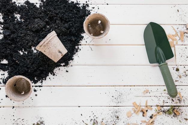 Вид сверху на лопату; горшочки с торфом для рассады; и почва над грязной деревянной скамейкой