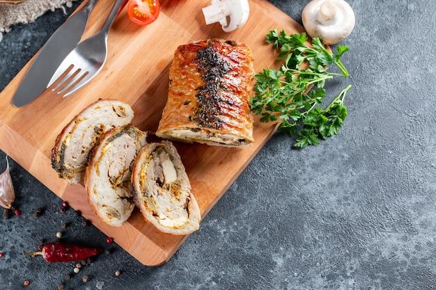 スライスしたローストポークルラードの俯瞰図-ポルケッタ、石の背景にイタリア料理の休日の伝統のおいしいポークロースト、クローズアップ、フラットレイ、コピースペース
