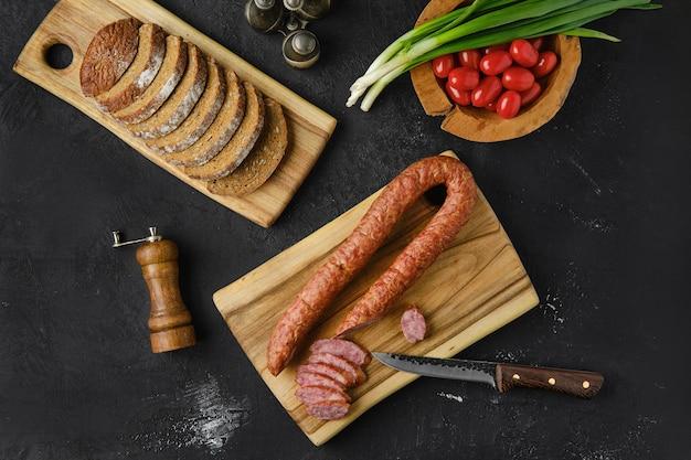 Вид сверху копченых колбасных колбас из баранины на деревянной разделочной доске на кухонном столе