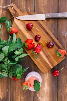 Overhead view of smoothie; mint leaf near cherries and strawberries on cutting board