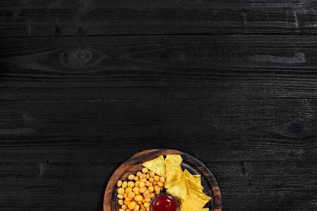 黒い木製のテーブルの上のソースとスナックの俯瞰図