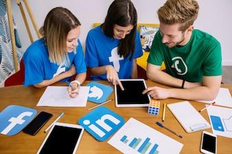 Overhead view of social media networking team looking at digital tablet