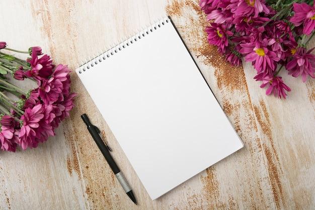 木製の背景にペンとピンクの花と螺旋状のメモ帳のオーバーヘッドビュー