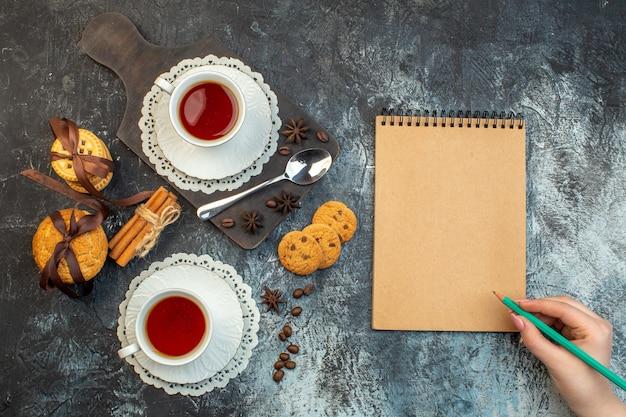 나무 커팅 보드에 쌓인 쿠키 계피 라임과 얼음 배경에 있는 노트북에 펜을 들고 있는 차 손의 오버헤드 보기