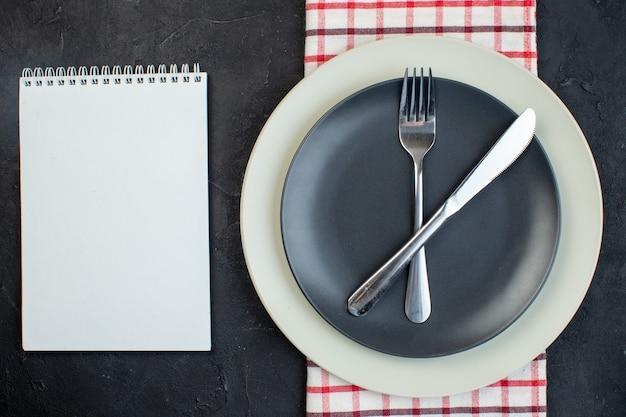 검은색 바탕에 여유 공간이 있는 빨간색 벗겨진 수건 공책에 있는 짙은 회색 색상과 흰색 빈 접시에 설정된 스테인리스 칼 붙이의 오버 헤드 보기