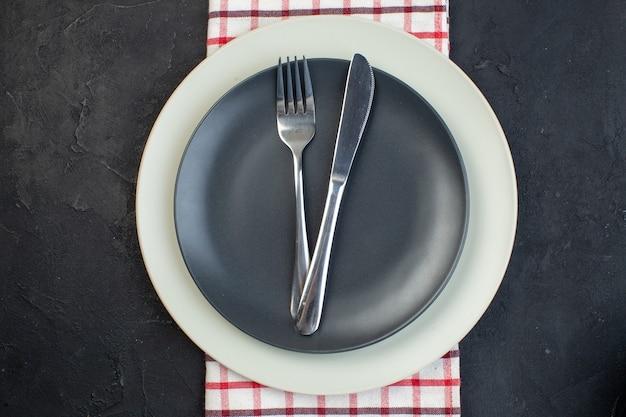 검은색 바탕에 여유 공간이 있는 빨간색 벗겨진 수건에 짙은 회색 색상과 흰색 빈 접시에 설정된 스테인리스 칼 붙이의 오버 헤드 보기