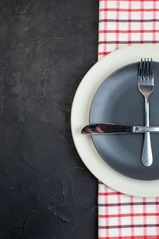 검은색 바탕에 빨간색 벗겨진 수건에 짙은 회색 색상과 흰색 빈 접시에 설정된 스테인리스 칼 붙이의 오버 헤드 보기