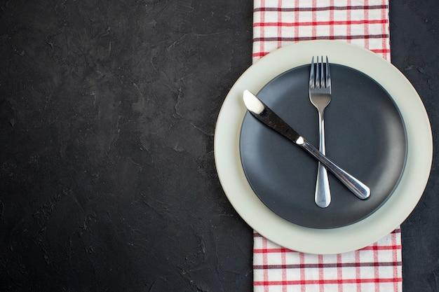 검은색 바탕에 여유 공간이 있는 왼쪽에 있는 빨간색 벗겨진 수건에 짙은 회색 색상과 흰색 빈 접시에 설정된 스테인리스 칼 붙이의 오버 헤드 보기